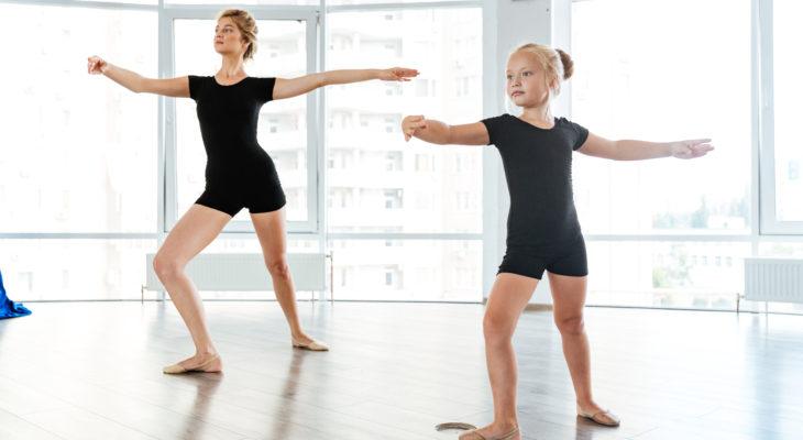 Little girl ballerina dancing with teacher in dance studio